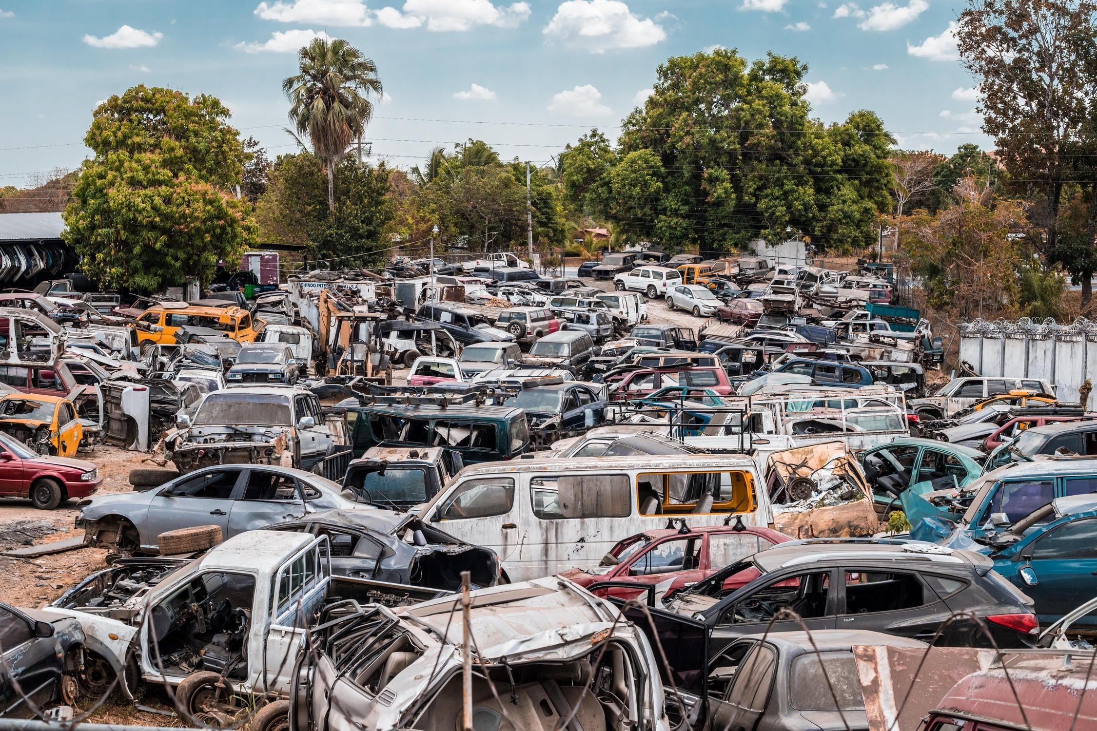 Assorted scrap cars parked in a junkyard