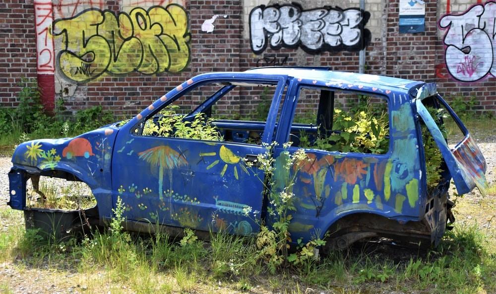 A scrap car sitting idly on a grassy property