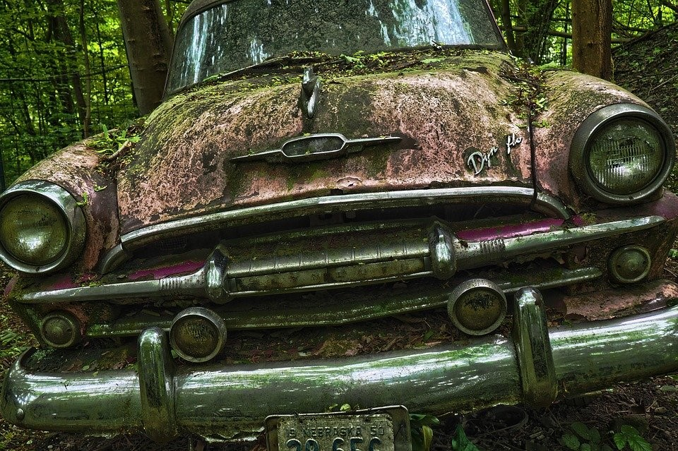dilapidated car in the middle of nowhere